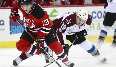 New Jersey Devils left wing Michael Cammalleri (13) races with the puck as Colorado Avalanche center Nathan MacKinnon (29) defends during the second period of an NHL hockey game, Tuesday, Feb. 14, 2017, in Newark, N.J. (AP Photo/Julio Cortez)