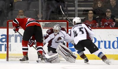 Colorado Avalanche goalie Jeremy Smith, center, stops a shot by New Jersey Devils right wing Stefan Noesen, left, as defenseman Mark Barberio (45) helps protect the net during the first period of an NHL hockey game, Tuesday, Feb. 14, 2017, in Newark, N.J. (AP Photo/Julio Cortez)