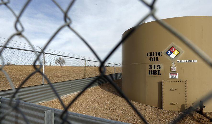 FILE - In this Feb. 13, 2017 file photo, a crude oil storage tank sits behind a fence at a petroleum extraction site, a few miles from the border of Boulder County, in Weld County, near Mead, Colorado. Colorado Attorney General Cynthia Coffman asked a state court Tuesday, Feb. 14, 2017 to overturn Boulder County's moratorium on oil and gas drilling, saying it violates state law and a state Supreme Court ruling. (AP Photo/Brennan Linsley, file)