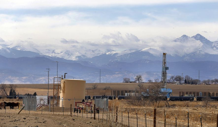 FILE - In this Feb. 13, 2017 file photo, a petroleum industry storage tank borders a ranch, left, near a fossil fuel extraction site, right, with the Front range of the Rocky Mountains rising up in the background, a few miles from the border of Boulder County, in Weld County, near Mead, Colorado. Colorado Attorney General Cynthia Coffman asked a state court Tuesday, Feb. 14, 2017 to overturn Boulder County's moratorium on oil and gas drilling, saying it violates state law and a state Supreme Court ruling. (AP Photo/Brennan Linsley, file)