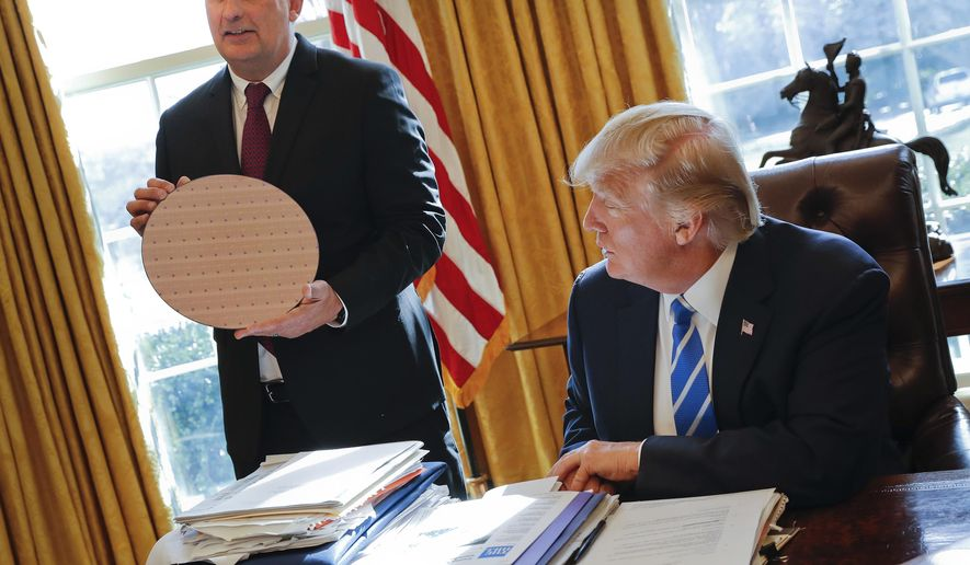 File - In this Feb. 8, 2017, file photo, President Donald Trump looks at Intel CEO Brian Krzanich, holding a silicon wafer, during their meeting in the Oval Office of the White House in Washington. When the CEO of Intel appeared at the White House to announce a revived effort to build a factory in Chandler, he talked about the need for more favorable tax policies under the Trump administration. The company also stands to get a big tax break at the state level under a legislation introduced in Arizona that was designed for big manufacturing corporations like Intel. (AP Photo/Pablo Martinez Monsivais, File)