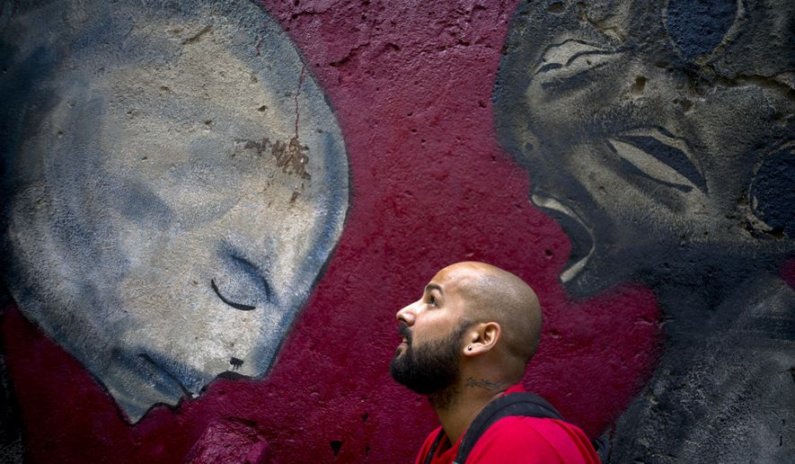 In this Feb. 9, 2017 photo, graffiti artist Yulier Rodriguez Perez poses with one of his works, painted on a wall in Old Havana, Cuba. Three years ago, the whimsical designs of the 27-year-old artist with the signature Yulier P. began to appear on walls in Havana where graffiti is rare. (AP Photo/Ramon Espinosa)