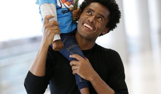 Olympic silver medalist Feyisa Lilesa, holds his son Sora, 3, while picking up his family at Miami International Airport, Tuesday, Feb. 14, 2017, in Miami. Lilesa arrived in the U.S. on a special skills visa, which allows him to train and compete until January. His wife, son, daughter and brother joined him in Miami Tuesday. (AP Photo/Wilfredo Lee)