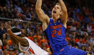 Florida guard Canyon Barry (24) is fouled by Auburn guard T.J. Dunans (4) during the first half of an NCAA college basketball game, Tuesday, Feb. 14, 2017, in Auburn, Ala. (AP Photo/Butch Dill)