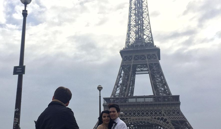 Lile Araus, from Panama city, right, and Alla Araus, from Ukraine, both living in Asheville, North Carolina pose in front of the Eiffel Tower in Paris, Tuesday, Feb. 14, 2017. It's a drizzly day in Paris but that didn't stop lovers from around the world celebrating Valentine's Day romance in the City of Light. (AP Photo/Nadine Achoui-Lesage)