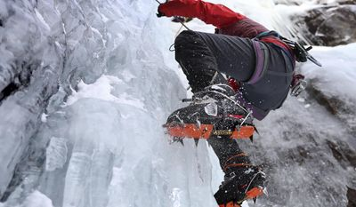 In this Sunday, Feb. 6, 2017 photo, a climber kicks the front points of her crampons into the ice while working her way up a route on Frankenstein Cliff in Hart's Location, N.H. (AP Photo/Robert F. Bukaty)