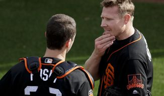San Francisco Giants relief pitcher Mark Melancon, right, talks to catcher Buster Posey during spring baseball practice in Scottsdale, Ariz., Tuesday, Feb. 14, 2017. (AP Photo/Chris Carlson)