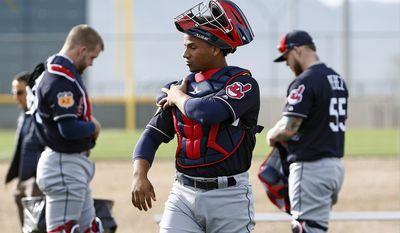 Cleveland Indians catchers Adam Moore, left, Francisco Mejia, center, and Roberto Perez, right, get their gear on at the Indians baseball spring training facility Tuesday, Feb. 14, 2017, in Goodyear, Ariz. (AP Photo/Ross D. Franklin)