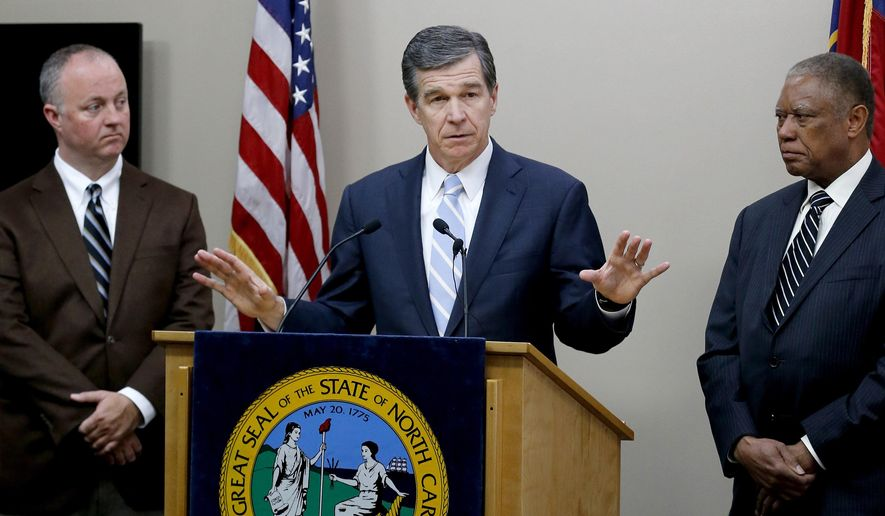 North Carolina Gov. Roy Cooper, center, holds a press conference  in Raleigh, N.C., Tuesday, Feb. 14, 2017, with House Democratic leader Darren Jackson, left, and state Senate Democratic leader Dan Blue, to say he will offer a compromise bill to Republicans so that HB2 can be repealed. (Chris Seward/The News & Observer via AP)