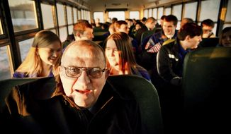 In this Jan. 14, 2014 photo, longtime Chisholm, Minn., High School boys basketball coach Bob McDonald rides the bus with his team as they travel to nearby Nashwauk-Keewatin for a matchup. The Minnesota Boys' Basketball Coaches Association on Monday, Feb. 13, 2017, announced the creation of the McDonald Award, named after retired coach Bob McDonald, who amassed 1,012 victories in 59 years at Chisholm High School. The award will be given for the first time following the 2017-18 season.  (Ben Garvin/Pioneer Press via AP)