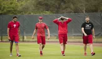 Philadelphia Phillies from left, Zach Eflin, Aaron Nola, Jerad Eickhoff, Alec Asher move in-between running drills during a spring training baseball workout Monday, Feb. 13, 2017 in Clearwater, Fla. (AP Photo/Matt Rourke)