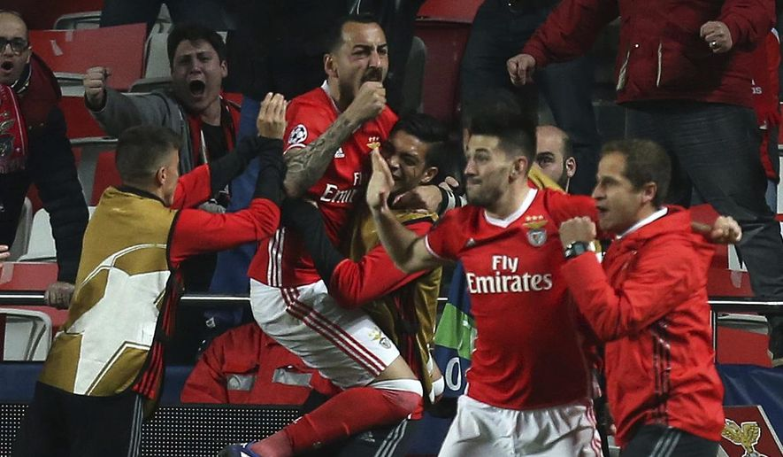 Benfica's Kostas Mitroglou celebrates with teammates scoring the opening goal during the Champions League round of 16, first leg, soccer match between Benfica and Borussia Dortmund at the Luz stadium in Lisbon, Tuesday, Feb. 14, 2017. (AP Photo/Armando Franca)