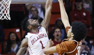Oklahoma guard Rashard Odomes (1) blocks a shot by Texas forward Jarrett Allen (31) during the second half of an NCAA college basketball game in Norman, Okla., Tuesday, Feb. 14, 2017. Oklahoma won 70-66. (AP Photo/Sue Ogrocki)