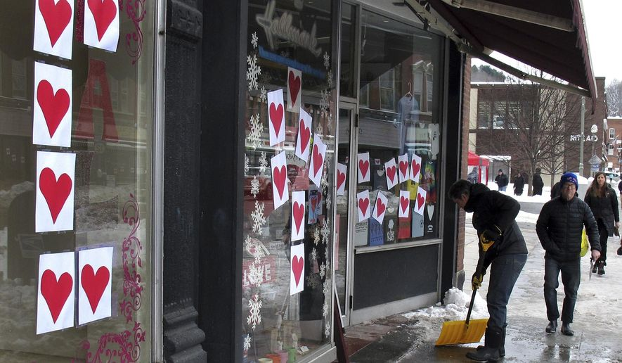 Eric Bigglestone shovels in front of his family business Capital Stationers in Montpelier, Vt., on Tuesday Feb. 14, 2017. Hundreds of red hearts were taped to windows throughout Montpelier. The Valentines Day tradition goes back years in the Vermont capital. (AP Photo/Wilson Ring)