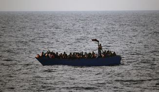 In this Friday, Feb. 3, 2017, file photo, migrants and refugees wave for help from inside a wooden boat 21 miles north of Sabratha, Libya. The chief of the European border and coast guard agency says migrant deaths in the Mediterranean on the Libya-to-Italy smuggling route have increased to a record level despite ever more rescue vessels trying to prevent mass drownings. (AP Photo/Emilio Morenatti, File)