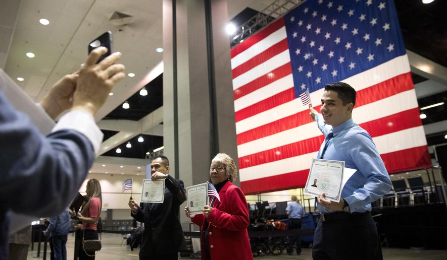 Erik Danialian, a 21-year-old immigrant from Iran, poses with his U.S citizenship certificate in front of a large U.S. flag after a naturalization ceremony at the Los Angeles Convention Center, Wednesday, Feb. 15, 2017, in Los Angeles. About 3,000 people took the oath in the morning and more than 3,500 others were expected during an afternoon ceremony, according to U.S. Citizenship and Immigration Services officials. (AP Photo/Jae C. Hong)
