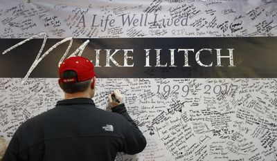 A well wisher signs a card for Mike Ilitch at Joe Louis Arena before an NHL hockey game between the Detroit Red Wings and St. Louis Blues, Wednesday, Feb. 15, 2017, in Detroit. Billionaire businessman Ilitch, who founded the Little Caesars pizza empire before buying the Detroit Red Wings and Detroit Tigers died Friday. He was 87. (AP Photo/Paul Sancya)