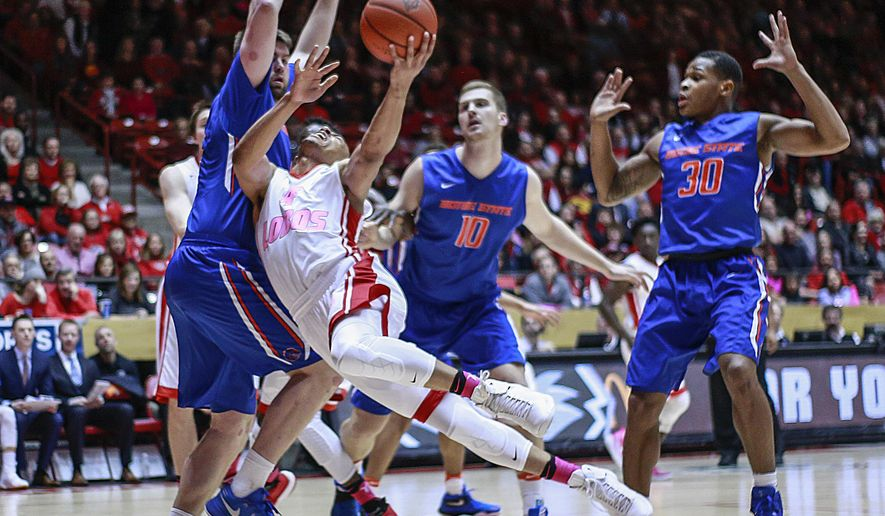 New Mexico's Elijah Brown (4) is fouled while driving to the basket against Boise State's Nick Duncan, left, Robin Jorch (10) and Paris Austin (30) during the first half of an NCAA college basketball game in Albuquerque, N.M., Tuesday, Feb. 14, 2017. (AP Photo/Juan Antonio Labreche)