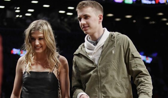 Genie Bouchard, walks the court with her blind date, John Goehrke, right, during the first half of an NBA basketball game between the Brooklyn Nets and the Milwaukee Bucks Wednesday, Feb. 15, 2017, in New York. After losing a Super Bowl bet on Twitter Bouchard agreed to go on a date with a random fan. (AP Photo/Frank Franklin II)