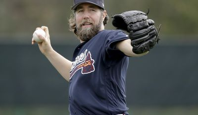 Atlanta Braves pitcher R.A. Dickey warms up at a baseball spring training workout, Wednesday, Feb. 15, 2017, in Lake Buena Vista, Fla. (AP Photo/John Raoux)