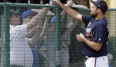 Atlanta Braves relief pitcher Josh Collmenter, right, signs autographs for fans at a baseball spring training workout, Wednesday, Feb. 15, 2017, in Lake Buena Vista, Fla. (AP Photo/John Raoux)