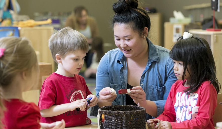 In this Tuesday, Feb. 14, 2017, photo, preschool teacher Theresa Phan, center, works with her students, including Cecilia Solorio, right, and Sawyer Wasserburger, on creating patterns in her classroom at Bright Horizons Family Solutions at Centennial Mall in Lincoln, Neb. The Nebraska Early Childhood Workforce Commission is beginning a comprehensive three-year collaboration to solve the most pressing issues facing early childhood education.  (Kristin Streff/The Journal-Star via AP)