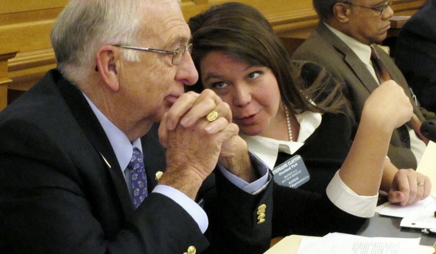 Kansas state Rep. Jim Karleskint, left, R-Tonganoxie, confers with Rep. Stephanie Clayton, center, R-Overland Park, during a House committee discussion on preventing concealed guns in public hospitals, Wednesday, Feb. 15, 2017, at the Statehouse in Topeka, Kan. Sitting to their right is Rep. Broderick Henderson, D-Kansas City (AP Photo/John Hanna)