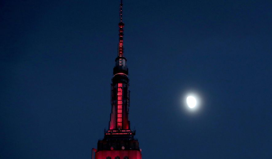 FILE - In this Thursday, Nov. 10, 2016, file photo, the moon is seen in its waxing gibbous stage as it rises near the Empire State Building, in New York. On Wednesday, Feb. 15, 2017, the Federal Reserve Bank of New York issues its Empire State manufacturing index for February. (AP Photo/Julio Cortez, File)