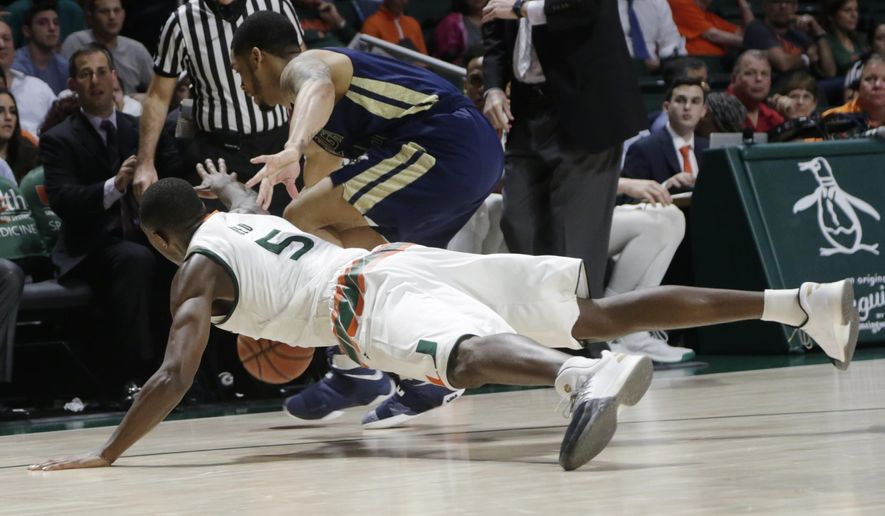 Miami's Davon Reed (5) reaches for the ball in front of Georgia Tech's Tadric Jackson, right, during the first half of an NCAA college basketball game, Wednesday, Feb. 15, 2017, in Coral Gables, Fla. (AP Photo/Lynne Sladky)