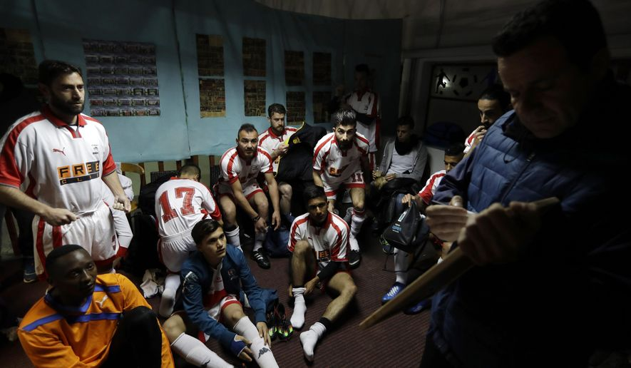 FOR STORY: GREECE TEAM CALLED HOPE - In this Sunday, Feb. 5, 2017, coach of Hope Refugee Football Club Antreas Sampanis, right, gives directions to his players before a soccer match in western Athens. On weekends they play in an amateur league against teams made up of professional groups like lawyers, telecom workers, and accountants. (AP Photo/Thanassis Stavrakis)