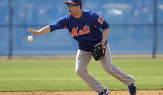 New York Mets second baseman Neil Walker tosses the ball to second base during a spring training baseball workout Wednesday, Feb. 15, 2017, in Port St. Lucie, Fla. (AP Photo/David J. Phillip)