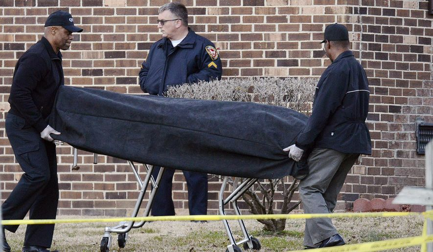 First responders remove a body from the scene after a police officer has shot and killed a man Wednesday, Feb. 15, 2017, in Durham, N.C. It was the second shooting by law enforcement in Durham in the past three days. (Bernard Thomas/The Herald-Sun via AP)