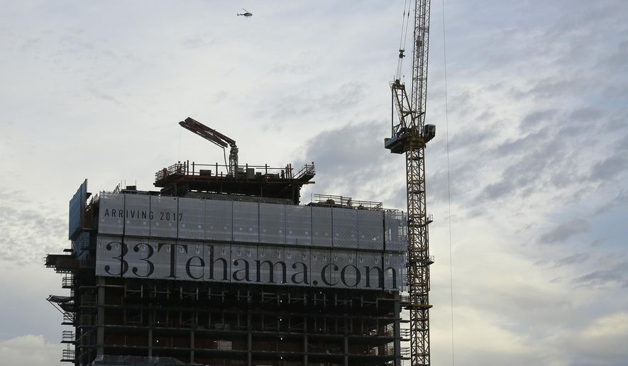 A helicopter flies over a luxury apartment high-rise building under construction on Tehama Street, Wednesday, Feb. 15, 2017, in San Francisco. Several office buildings in San Francisco's South of Market neighborhood have been evacuated after a large unstable concrete slab started tilting and a crane atop the skyscraper malfunctioned on Wednesday. (AP Photo/Eric Risberg)