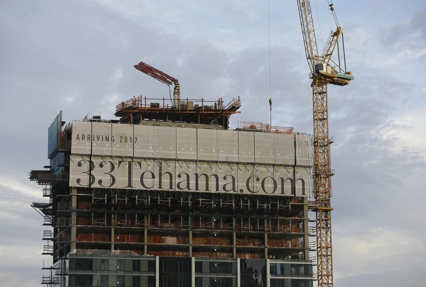 A luxury apartment high-rise building is under construction on Tehama Street, Wednesday, Feb. 15, 2017, in San Francisco. Several office buildings in San Francisco's South of Market neighborhood have been evacuated after a large unstable concrete slab started tilting and a crane atop the skyscraper malfunctioned on Wednesday. (AP Photo/Eric Risberg)