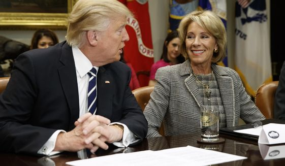 President Donald Trump looks at Education Secretary Betsy DeVos as he speaks during a meeting with parents and teachers, Tuesday, Feb. 14, 2017, in the Roosevelt Room of the White House in Washington. (AP Photo/Evan Vucci)
