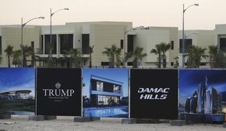 In this Sunday, Feb. 12, 2017, file photo, a new sign sits on display for the Trump International Golf Club in Dubai, United Arab Emirates. U.S. President Donald Trump's two sons in charge of his business empire will attend a closed-door event to mark the opening of the Trump International Golf Club in Dubai. (AP Photo/Jon Gambrell, File)