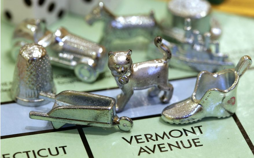 In this Feb. 5, 2013 file photo, the thimble game piece, left, sits among other Monopoly tokens at Hasbro Inc., headquarters in Pawtucket, R.I. The thimble will no longer be a game piece in Monopoly, rejected in 2017 in a campaign to determine the tokens for the next generation of the game. (AP Photo/Steven Senne, File)