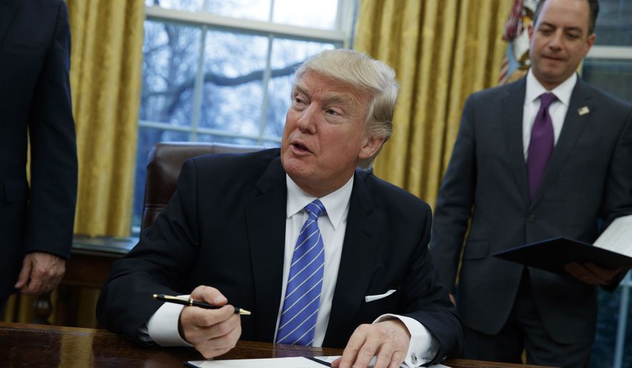 President Donald Trump signs an executive order to withdraw the U.S. from the Trans-Pacific Partnership trade pact agreed to under the Obama administration in the Oval Office of the White House in Washington on Jan. 23, 2017. (Associated Press) **FILE**