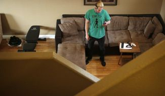 Randy Tussing, an Airbnb host, looks at his phone while standing in his home, Thursday, Feb. 16, 2017, in Las Vegas. More than 340,000 people passed on Nevada's hotel rooms last year and opted instead to book a place to stay using the home-sharing service Airbnb. The $47 million in revenue that hosts took in is a loss for the state's hospitality industry that one expert says will only increase if not addressed. (AP Photo/John Locher)
