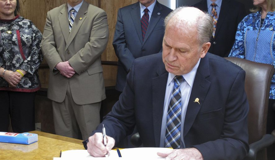 Alaska Gov. Bill Walker signs an administrative order outlining measures aimed at combating opioid abuse in Alaska on Thursday, Feb. 16, 2017, in Juneau, Alaska. Walker this week issued a public health disaster declaration stemming from the abuse of opioids in Alaska. (AP Photo/Becky Bohrer)