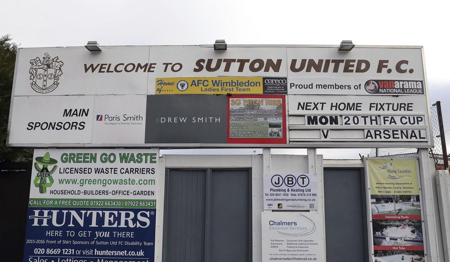 A sign advertising Sutton United's next fixture, which is against Arsenal on Monday 20th Feb, 2017 at Gander Green Lane, London, Thursday Feb. 16, 2017. Sutton United, the fifth-tier semiprofessional team will play Arsenal, the 13-time English champions, after reaching the fifth round of the FA Cup competition for the first time in its 118-year history on Monday Feb. 20, (Andrew Matthews/PA via AP)