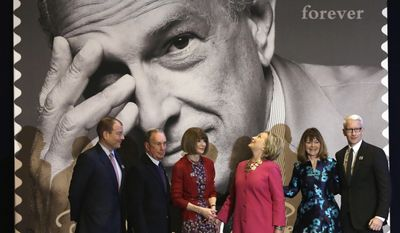 Hillary Clinton, third from right, looks at one of the Oscar de la Renta stamps unveiled during ceremonies in Grand Central Terminal, in New York, Thursday, Feb. 16, 2017. Also in attendance is, from left, Oscar de la Renta CEO Alexander Bolen, Michael Bloomberg, Vogue Editor Anna Wintour, Clinton, U.S. Postal Service Vice President Janice Walker and journalist Anderson Cooper. Clinton has praised Oscar de la Renta as an inspiration to striving immigrants like himself at an event honoring the late fashion designer with a series of commemorative stamps. (AP Photo/Richard Drew)
