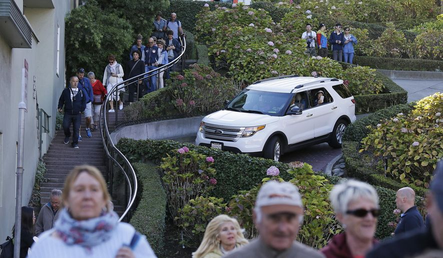 "FILE - In this Sept. 21, 2016, file photo, tourists make their way down Lombard Street, also known as the ""most crooked street"" in San Francisco. A San Francisco supervisor is calling for a toll on the famously crooked street that has become too popular with tourists and creates headaches for residents. (AP Photo/Eric Risberg, File)"