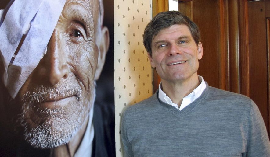 Job Heintz, of the Himalayan Cataract Project, stands beside a photo of one of the organization's patients, Thursday Feb. 16, 2017, in Waterbury, Vt. The Vermont-based nonprofit group that works to cure blindness in Nepal and other countries in the developing world is one of eight semi-finalists for a $100 million grant from the John D. and Catherine T. MacArthur foundation. (AP Photo/Wilson Ring)