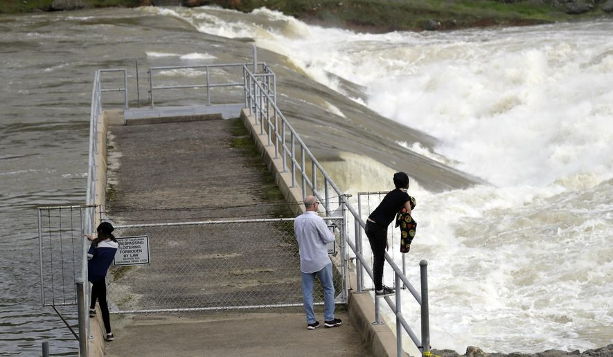 People watch the gushing waters of the Feather River from the town's fish hatchery a day after an evacuation was lifted Wednesday, Feb. 15, 2017, in Oroville, Calif. Authorities say the immediate danger has passed and allowed people living downstream of the Oroville Dam to go back home Tuesday after ordering an evacuation Sunday. But new storms forecast to hit Northern California this week will test quick repairs to the dam.  (AP Photo/Marcio Jose Sanchez)