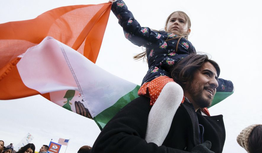 """Eva Marquez, 6, waves the flag of Mexico while riding on her father Marco's shoulders during a protest for a +Day Without Immigrants"""" protest Thursday, Feb. 16, 2017, in St. Paul, Minn. It was part of a nationwide rally designed to show how important immigrants are to daily life. (Evan Frost/Minnesota Public Radio via AP)"""