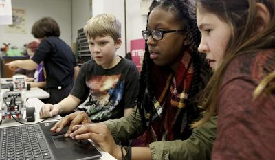 "In this Jan. 28, 2017 photo, Northern Illinois University service leader Keeayla Jones,  center, helps Max Law, left, and Brianna VanGarsse, during a Star Wars-themed STEM workshop titled ""From A Galaxy Far, Far Away"" at NIU in DeKalb, Ill. STEM is an acronym for science, technology, engineering and math. NIU's STEM Outreach program offers several classes throughout the year. The ""Star Wars"" themed workshop made this class one of the best-attended, STEM educator Jeremy Benson said. (Matthew Apgar/Daily Chronicle via AP)"