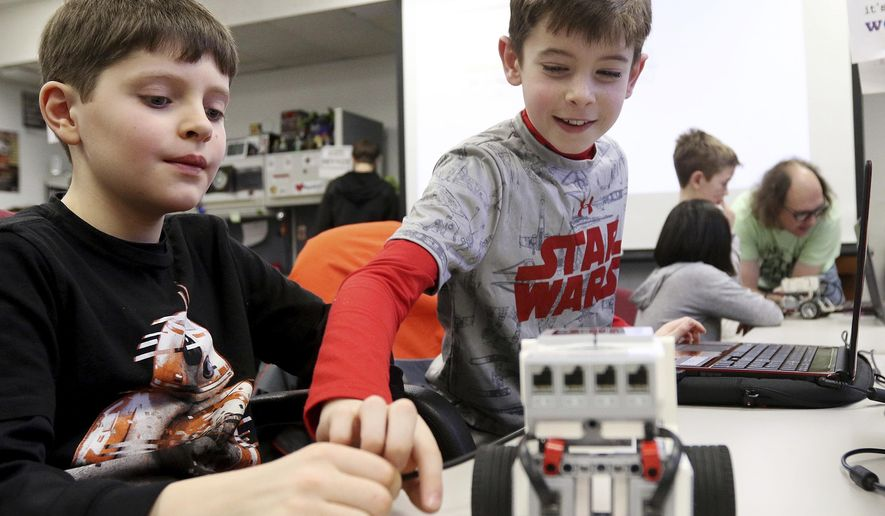 "In this Jan. 28, 2017 photo, Jack O'Neil, left, and Henry Sartell, work on a robot  during a Star Wars-themed STEM workshop titled ""From A Galaxy Far, Far Away"" at Northern Illinois University in DeKalb, Ill. STEM is an acronym for science, technology, engineering and math. NIU's STEM Outreach program offers several classes throughout the year. The ""Star Wars"" themed workshop made this class one of the best-attended, STEM educator Jeremy Benson said. (Matthew Apgar/Daily Chronicle via AP)"