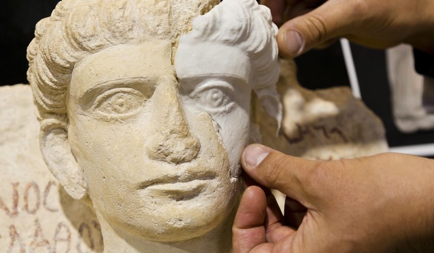 Restorer Antonio Iaccarino Idelson shows a computer-rendered, 3D print-generated replica of a missing part of a limestone male bust, dated between the 2nd and the 3rd century A.D. that was damaged during the Islamic State occupation of the Syrian city of Palmyra, in Rome, Thursday, Feb. 16, 2017. The replica is held in place with magnets. Two damaged sculptures from the National Museum of Palmyra were restored in Rome and will be brought back to Syria at the end of February. (AP Photo/Domenico Stinellis)