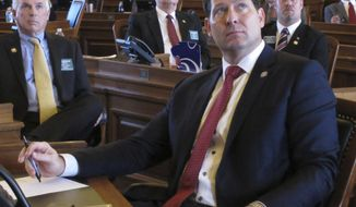 Kansas House Speaker Ron Ryckman Jr., R-Olathe, watches one of the chamber's electronic vote-tallying boards as members approve a bill increasing personal income taxes to help balance the state budget, Thursday, Feb. 16, 2017, at the Statehouse in Topeka, Kan. Republicans are split over the bill and Ryckman opposes it (AP Photo/John Hanna)